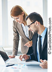 Computing - Image of two young business partners using...