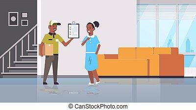 conceito, modernos, cheio, vivendo, carteiro, serviço, americano, uniforme, área de transferência, segurando, interior, apartamento, mulher, pacote, mensageiro, mostrando, expresso, entrega, papelão, recipiente, caixa, sala, comprimento, africano
