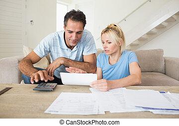 concentré, couple, à, factures, et, calculatrice, dans, salle de séjour