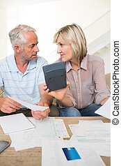 concentré, couples mûrs, à, factures, et, calculatrice, chez soi