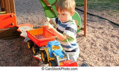concentré, garçon, peu, chargeur, sandbox, vidéo, 4k, enfantqui commence à marcher, jouer, caravane