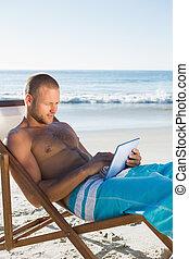 concentrado, bonito, homem, usando, seu, tabuleta, enquanto, sunbathing