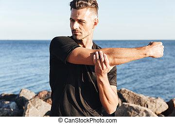 concentrado, desportista, fazendo, esticar, exercícios
