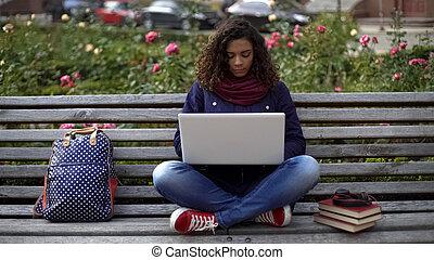 concentrado, estudiante, sentado, computador portatil, joven, banco, hembra, aire libre, estudio