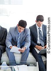 concentrado, pessoas negócio, sentando, e, esperando, para, um, entrevista trabalho, em, um, escritório