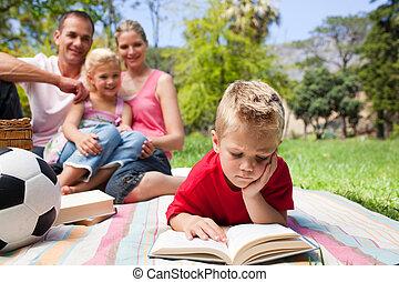 concentrado, rubio, lectura chico, mientras, tener un picnic, con, el suyo, familia , en, un, parque