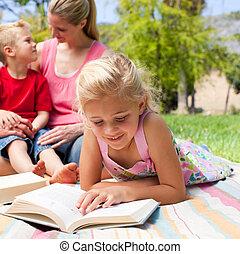 concentrado, rubio, lectura de la muchacha, mientras, tener un picnic, con, ella, familia , en, un, parque