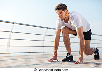Concentrared young sportsman is ready to run outdoors