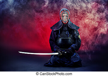 concentrate - Handsome young man practicing kendo. Over dark...
