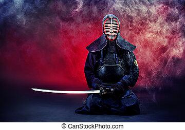 Handsome young man practicing kendo. Over dark background.