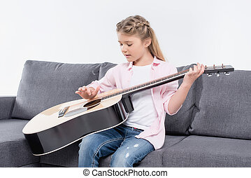 concentrated adorable caucasian girl playing on guitar while sitting on sofa