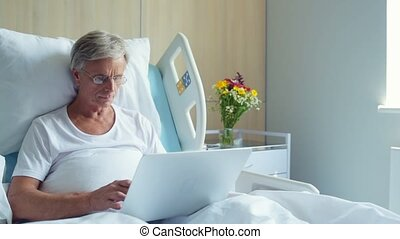 Concentrated aged man staying in the hospital ward