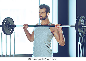 Concentrated and strong. Young handsome man in sportswear lifting barbell at gym