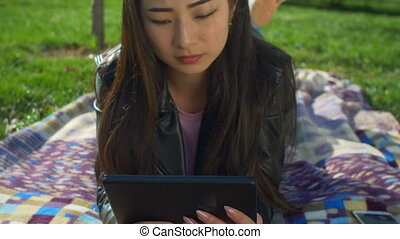 Concentrated asian girl working on tablet pc in park