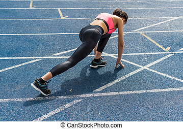Concentrated athletic young runner on starting line at running track stadium