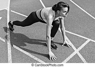 Concentrated athletic young runner on starting line at running track stadium, black and white photo