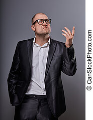 Concentrated bald business man looking up serious in eyeglasses and have an idea in suit on grey background. Closeup