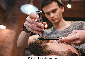 Concentrated barber making perfect beard to handsome bearded man