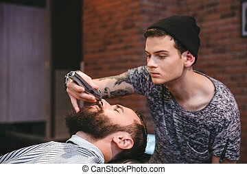 Concentrated barber trimming beard of handsome man in barbershop