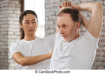 Concentrated bearded man stretching his arms