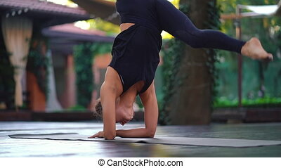 Concentrated beautiful girl in Bakasana. Strong hands. Handstand. Young woman with oriental appearance practicing yoga alone on wooden deck in tropical island.