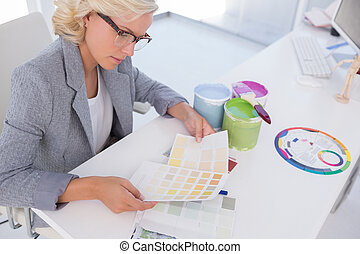 Concentrated blonde interior designer holding colour charts...