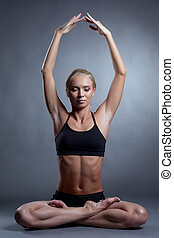 Concentrated blonde meditating in lotus position, on gray ...