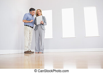 Concentrated blonde realtor showing an empty room and some...