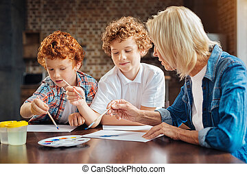 Concentrated brothers painting with granny at home