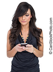 Concentrated brown haired model holding smartphone