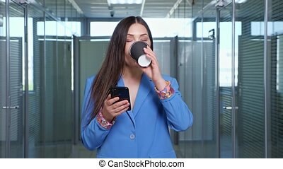 Concentrated brunette in blue jacket types on black smartphone and holds coffee cup standing in hall among offices against window close view