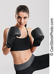Concentrated brunette sportswoman training in boxing gloves while looking on camera, over white background