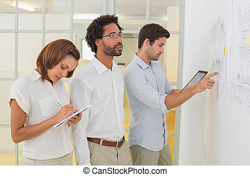 Concentrated business people using digital tablet in meeting