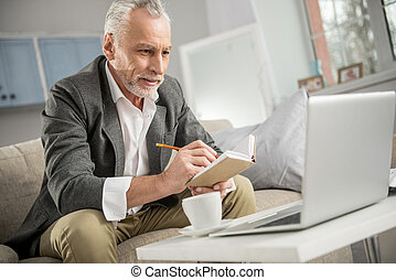 Concentrated businessman looking at his laptop