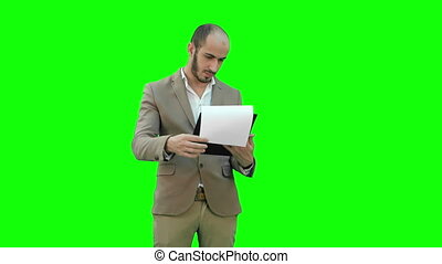 Concentrated businessman reading financial report on a Green Screen, Chroma Key.