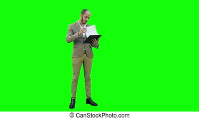 Concentrated businessman reading important report on a Green Screen, Chroma Key.