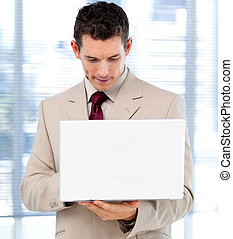 Concentrated businessman using a laptop standing