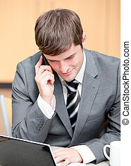 Concentrated businessman using his laptop while talking on phone at work