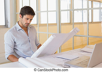 Concentrated businessman working on blueprints in office -...