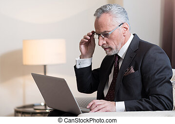 Concentrated businessman working with the laptop in the hotel