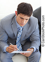 Concentrated businessman writing while waiting for a job interview in an office