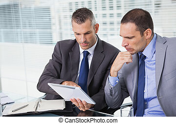 Concentrated businessmen analyzing documents on their tablet...