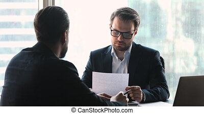Concentrated businessmen discussing paper contract in office, shaking hands making agreement, establishing partnership at business meeting. Male client thanking financial advisor for consultation.