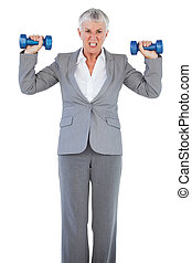 Concentrated businesswoman holding dumbbells