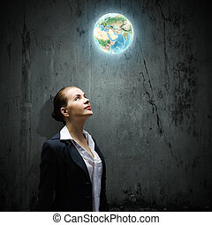 Image of thoughtful businesswoman looking at planet earth