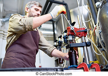 Concentrated busy brewer closing beer bottle at plant - Busy...