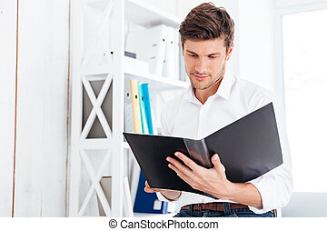 Concentrated busy businessman working with documents in...
