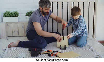 Concentrated child is sawing plywood sheet with hand saw and...