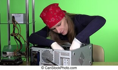 Concentrated computer service worker woman fix broken computer in the office. green wall background. 4K
