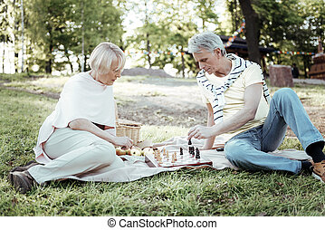 Concentrated couple sitting on the blanket